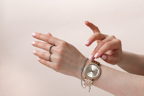 Woman adjusting watch and bracelets on hand