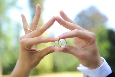 Hands holding wedding rings together forming infinity sign