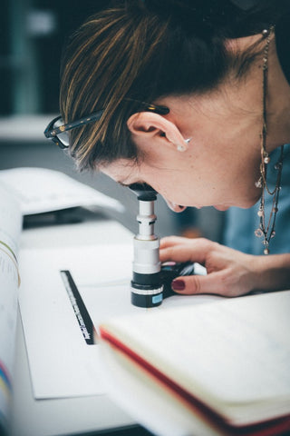 Woman inspecting jewelry on a table with microscope