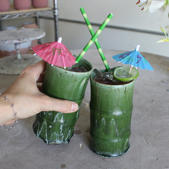 Green ceramic bamboo tumblers with paper bamboo straws and cocktail umbrellas on a gray background