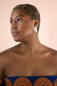 Beautiful brown girl wearing heavy sterling silver earrings casted from sea urchin spine.