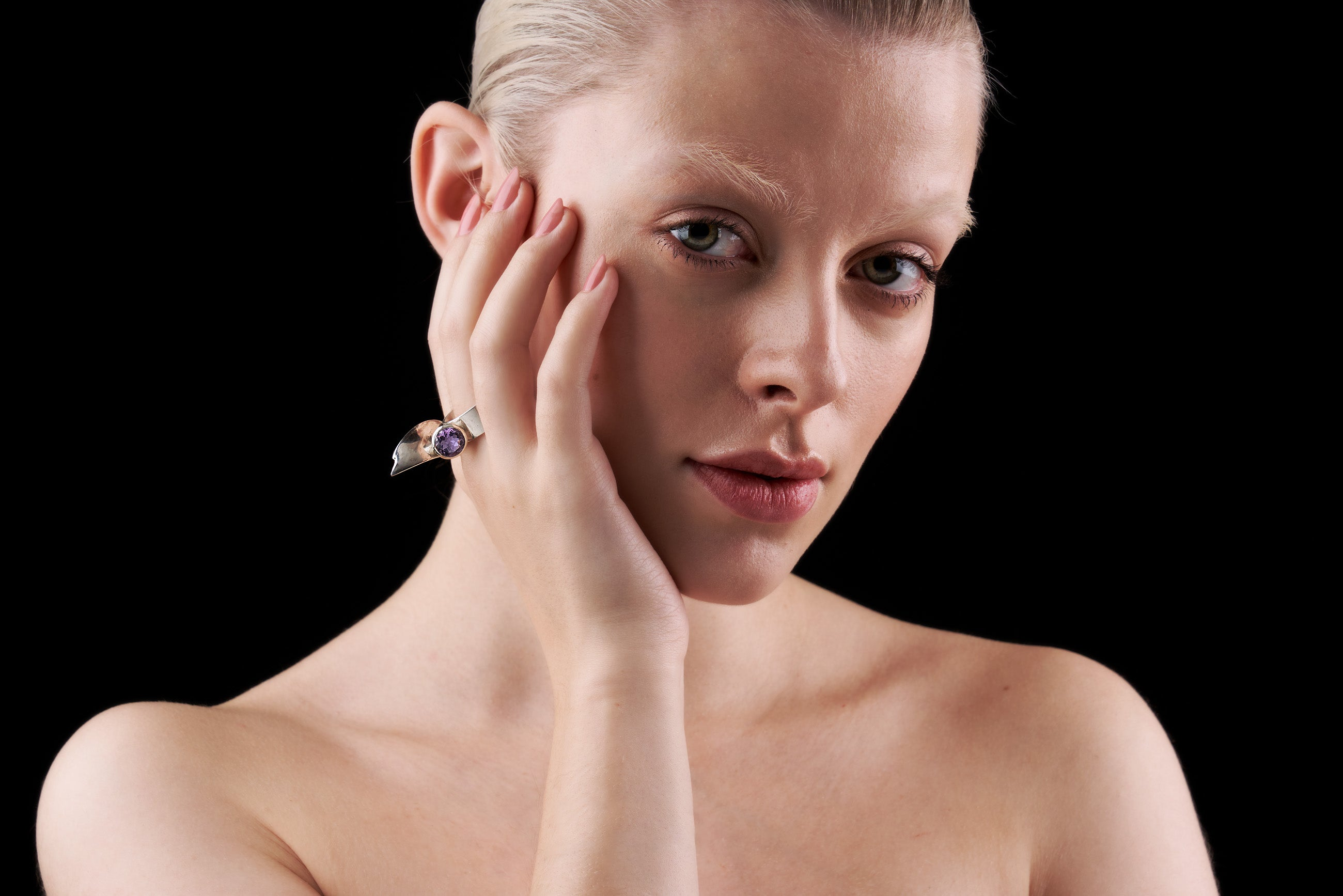 Beautiful girl wearing heavy sterling silver ring with faceted amethyst.