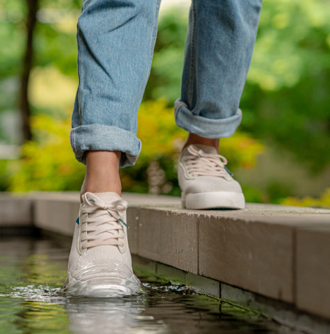 A person dipping their foot in the water, wearing Vessi Weekend waterproof shoes.