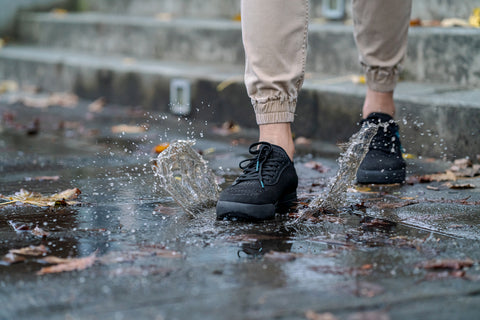 Someone walking on a wet, splashing sidewalk in their Vessi waterproof knit shoes