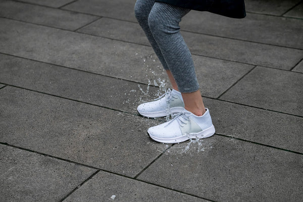 Person wearing Vessi rain shoes jumping on a puddle