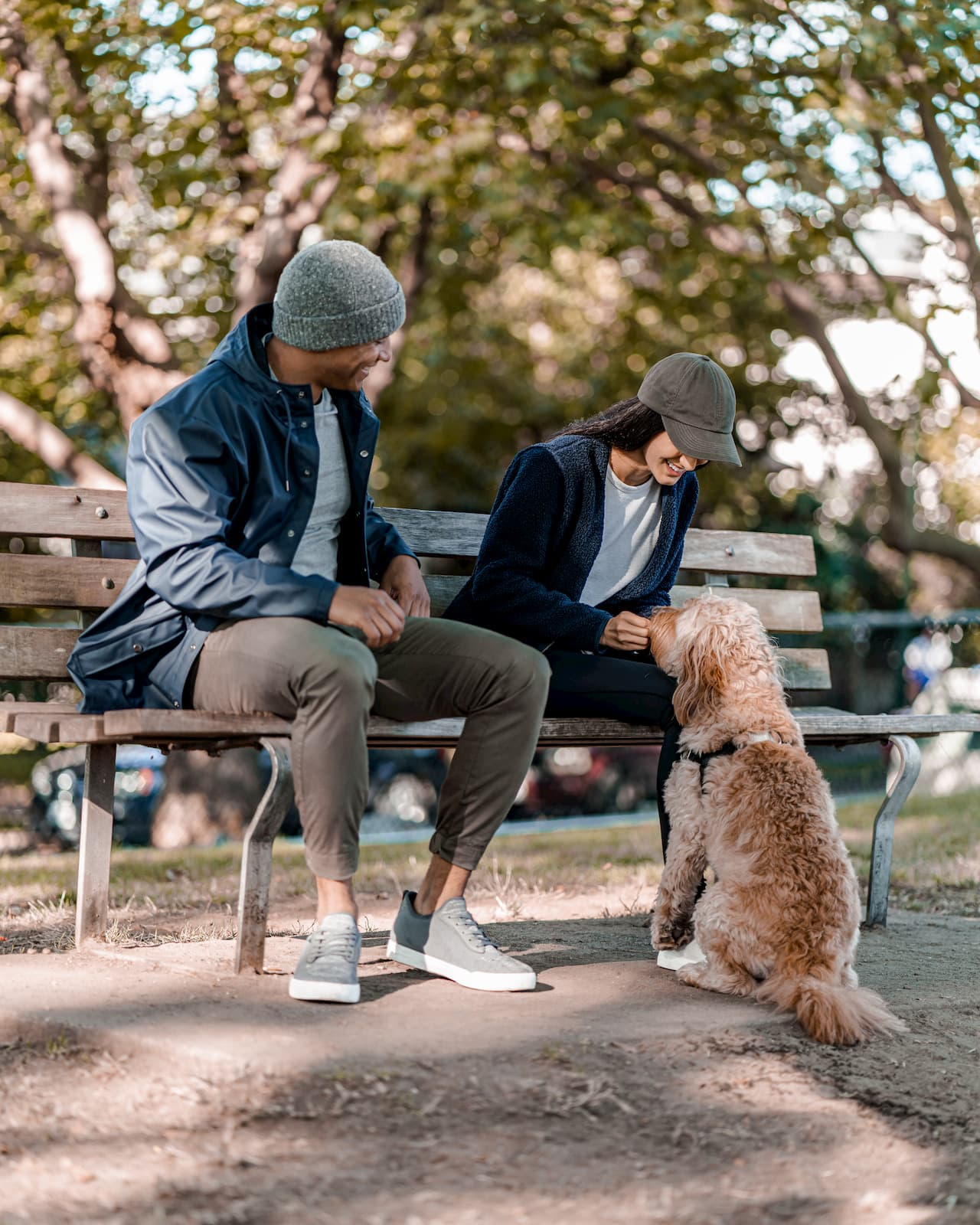 Man and woman sitting on a bench with their fluffy dog in the fall.