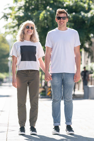 Man and woman holding hands and smiling wearing matching Vessi Weekend shoes.