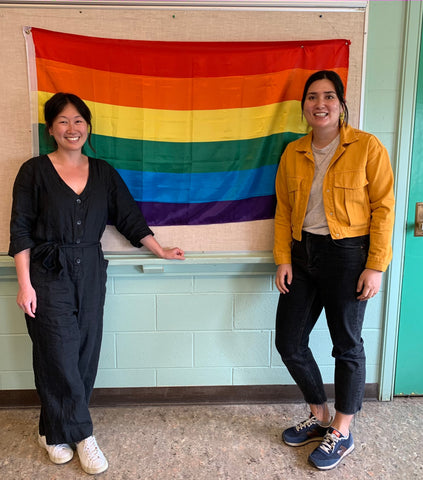 Two teachers in front of Pride flag