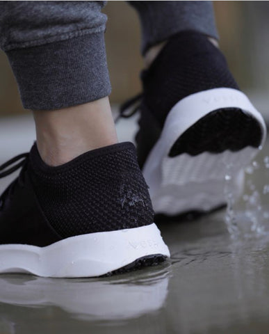 Close image of a woman's feet in comfortable shoes walking on a watery path