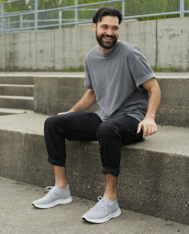 Image of a man sitting on a cement step comfortably wearing Vessi waterproof shoes