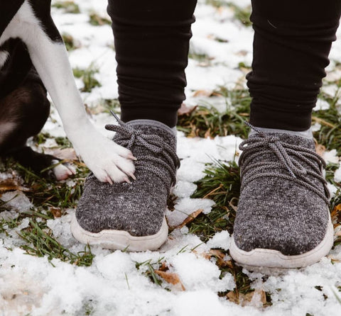 A person wearing Vessi shoes in the snow with a dog sitting next to them