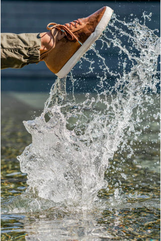 A person wearing Vessi knit sneakers kicking water in a lake showing how waterproof Vessis are.