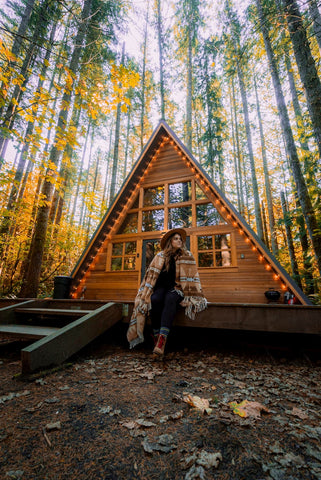 Woman wrapped up in a blanket sitting on a cabin patio in the fall.