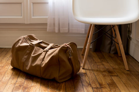 One brown leather duffle bag sitting on the wood floor next to a white stool, representing packing light