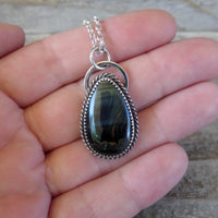 Blue tiger eye and sterling silver pendant on hand