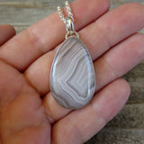 White lace agate and sterling silver pendant on hand