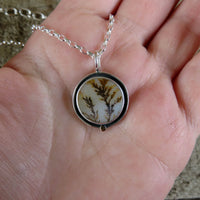 Dendritic agate shadowbox pendant with 14k gold accent on hand
