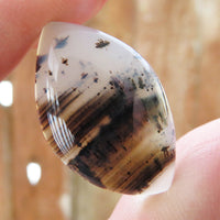 Large Montana agate cabochon held up to the light