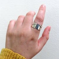 Wide band mountain ring on hand
