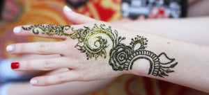 Henna design on hand with gold glitter