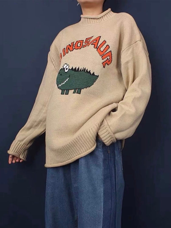 beige knitted sweater with a dinosaur drawn by a child with dinosaur written in orange above the dinosaur