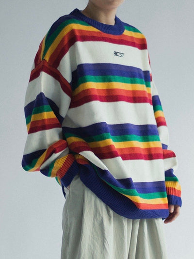 knitted sweater with rainbow lines between big white lines. Best is embroidered in black on the chest on a white line