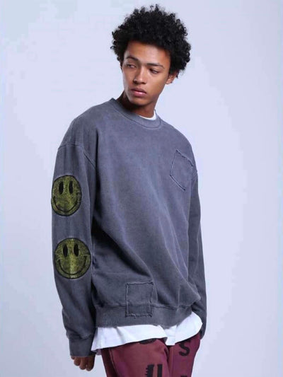 patched gray pullover with large yellow smiling faces on the sleeves and one in the upper back worn