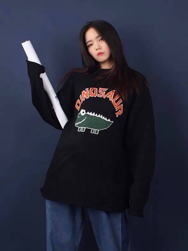 black knitted sweater with a dinosaur drawn by a child with dinosaur written in orange above the dinosaur