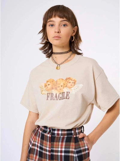beige tshirt with three angels printed on the front with the text below fragile in brown