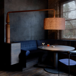 Juniper berry-blue furniture sits against blackened walls inside this cosy bar, laboratory and store that design studio YSG has created in Sydney for gin brand Four Pillars.
