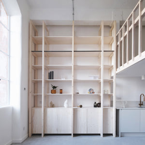 Structural ash and pine joinery – including a staircase, mezzanine and double-height storage wall – delineate the space within this refurbished, open-plan apartment in London by EBBA Architects.