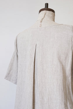 Flowy, slight oatmeal colored A-Line dress with elegant back pleat. Meant to be worn for every occasion, either alone as a dress or layered over pants.  Elbow length sleeves can easily be cuffed. V-neck. And yes, it has pockets!    100% medium weight European linen, prewashed.