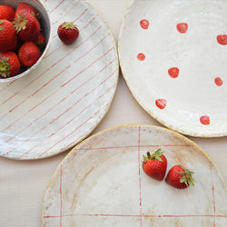 Handmade ceramic plates by Florence Penault in white glaze with painted red detailing