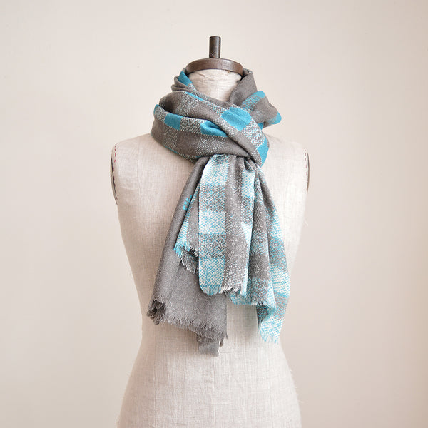Large wool scarf that has the luxurious feel of cashmere. Made by Epice Paris, this scarf is the perfect Fall accessory in a graphic plaid pattern on one end and solid ash on the other.
