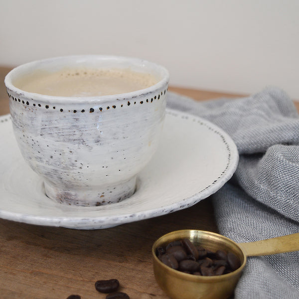 Adorable bowl and matching saucer by French artist Florence Penault. Sized perfectly for ice cream, a cup of soup, or a dip! Tiny hand painted black dots adorn the edges adding a touch of sophistication to the organic look of the glaze.
