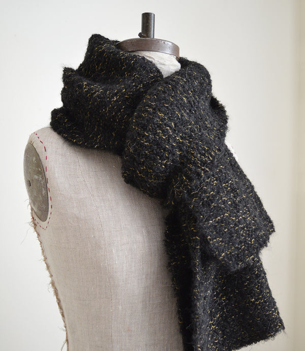 Made of the softest alpaca wool, these scarves are hand knit by a collective of mothers in Peru. Thick and chunky (perfect for the coldest weather) in black wool with subtle natural detailing.