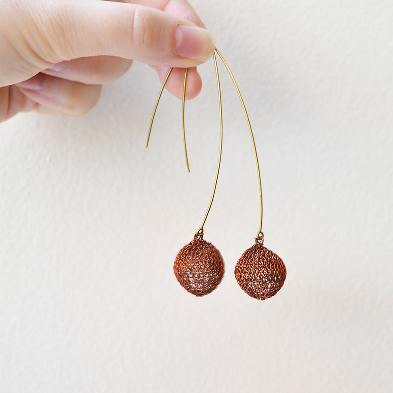 "Lotta Djossou Ligthweight wire earrings handcrafted by artisans in the island of Sumba in eastern Indonesia. Their wire wrapping technique produces delicate and timeless pieces that add a touch of sophistication to any look. About 3"" long. (Dark Copper and Gold spheres are the same size, silver spheres are slightly larger) Sumba Island, Indonesia"