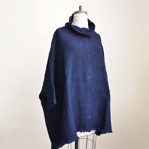 Auntie Oti Poncho. Woven in thick hand spun cotton yarns, this oversized pullover layers like a big comfy sweater with a slight cowl neck and 3/4 length sleeves. Garment dyed in dark natural indigo, one size. 100% cotton khadi.