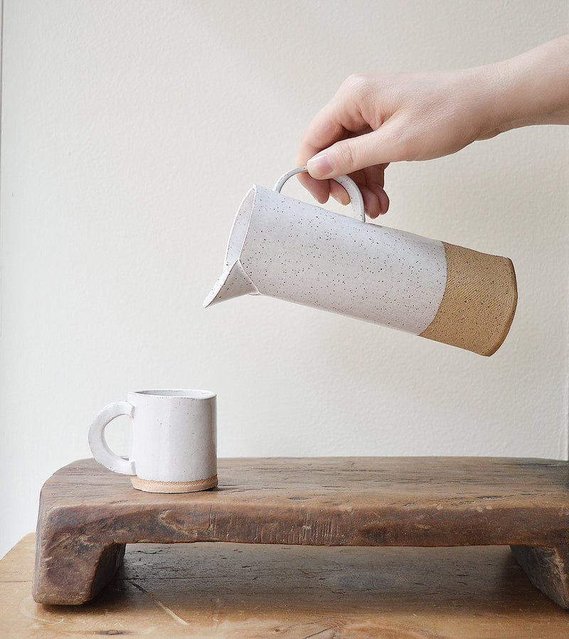 Handmade slender pitcher made from speckled stoneware with white glaze from Brooklyn-based ceramicist Alison Owen.  Perfect for serving your favorite beverages or styled as a vase, these pitchers make a striking yet understated statement.