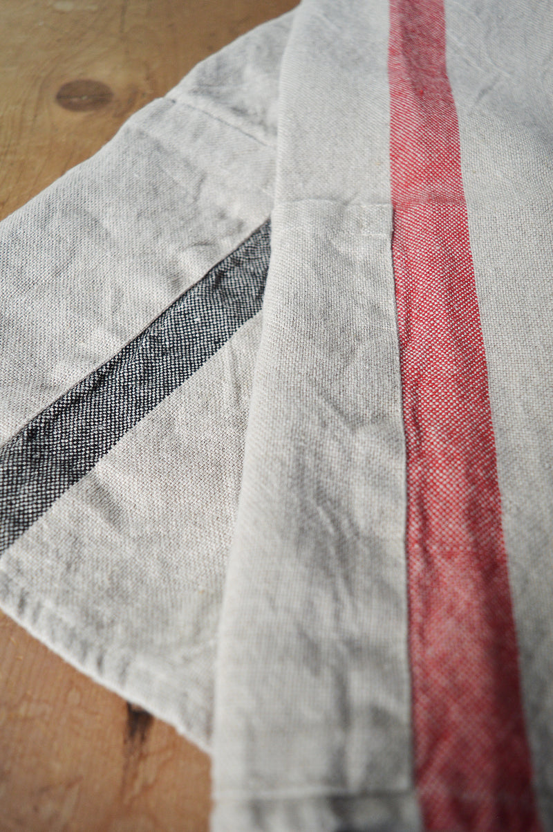 Half apron made of heavy weigh linen. An offset stripe and a large pocket divided in two make this utilitarian apron a durable and stylish kitchen companion.