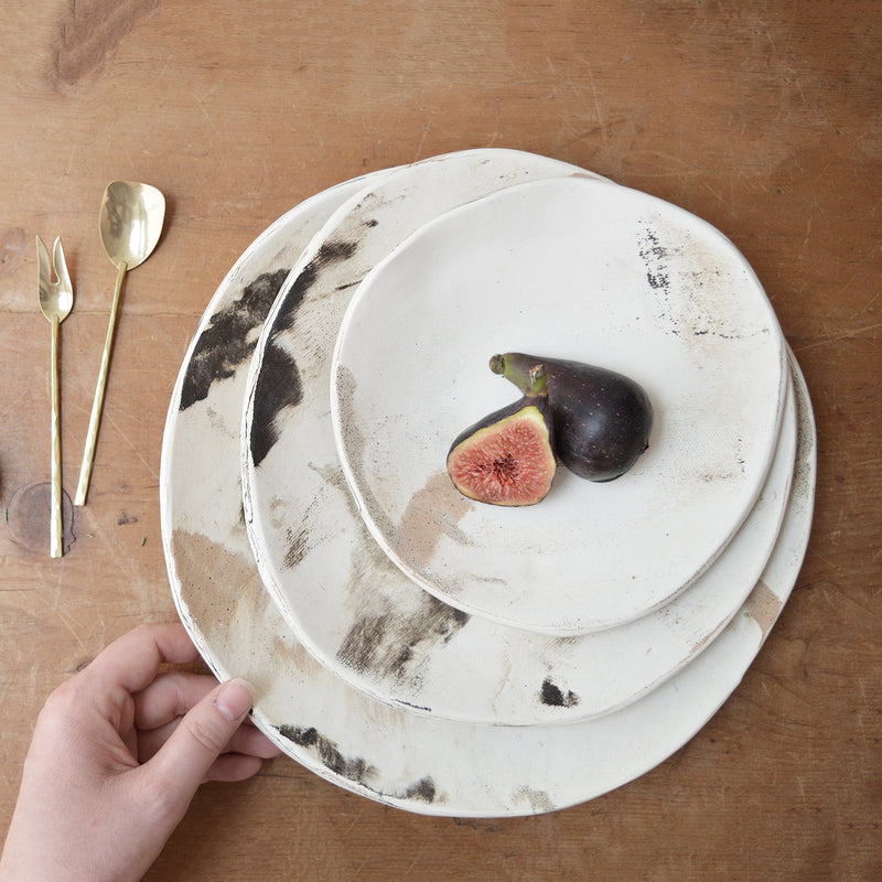 Set of 3 nesting plates with a painterly matte finish. Handmade in Savannah, GA by Jennifer Huskey. Jennifer combines porcelain, black clay and speckled stoneware clay to create these one-of-kind plates. Perfect to use as serving dishes or to eat in. One of a kind.