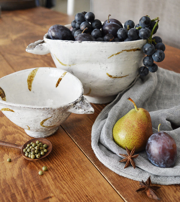 Large handmade ceramic bowls with pouring spout made by one of our favorite artists (and fellow French native), Florence Pénault.    Handmade in two sizes, these bowls feature a small pouring spout to making mixing and baking an ease with hand-painted half-moon details in a brownish-gold hue.
