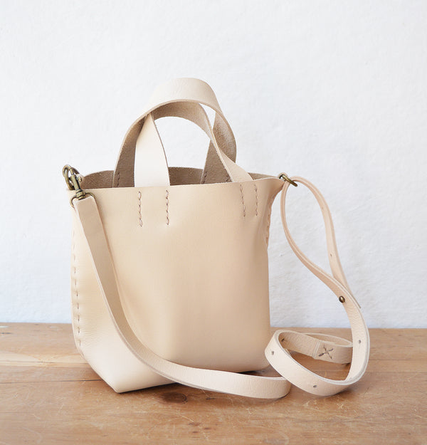 Stitch and Tickle mini bucket tote handmade of soft, medium weight, vegetable tanned leather. The leather will darken beautifully with age. Hand sewn. Made in Boston.