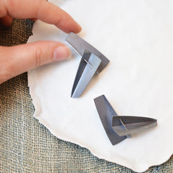 "Minimal in design, Lauren Markley's jewelry is eye-catching and artistic -these striking earrings are made from hand cut sterling silver in folded together to create intriguing planes and angles.   Folded sterling silver wedges with sterling silver posts.  Earrings measure approximately 2"" x 1""."