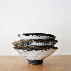 One of a kind ceramic bowls by Florence Penault. These are all finished with a dark glaze onto which a lose white brushstroke is artfully applied. Glossy finish. The finished glaze is reminiscent of a 14th century Korean technique, called Buncheong. Slightly oval shapes (see dimension below).