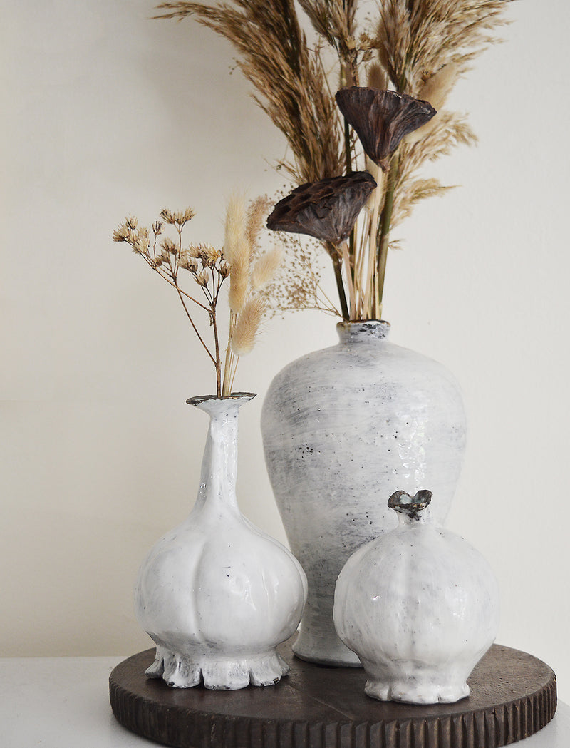 Inspired by the shape of poppy pods, these bud vases are made by one of our favorite artists (and fellow French native), Florence Penault. Glazed in the 14th century Korean Buncheong style, the color at the tip of the opening varies from green to blue with some dark metallic glaze.