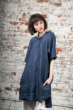 Flowy, slight indigo denim A-Line dress with elegant back pleat. Meant to be worn for every occasion, either alone as a dress or layered over pants.  Elbow length sleeves can easily be cuffed. V-neck. And yes, it has pockets!    100% medium weight European linen, prewashed.