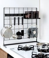 Alternate view of Black Grid Panel Organizer next to the stove with utensils, lids and spices on hooks and shelving attachments