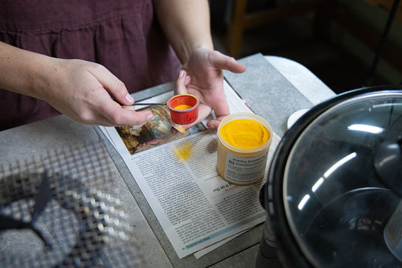 Sifting yellow enamel onto copper disk.  Photo by EGB Photography.
