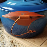 A side view of a brown leather cast iron assist handle holder showing fingertip protection down the side of a Dutch oven